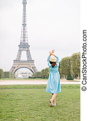 Back view of pretty lady in blue dress and hat, enjoying walk in Paris, near Eiffel tower. Young attractive happy woman with hands up facing the Eiffel Tower in Paris, France.
