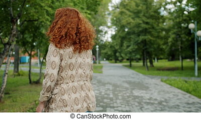 Back view of pretty redhead girl walking in park alone ...