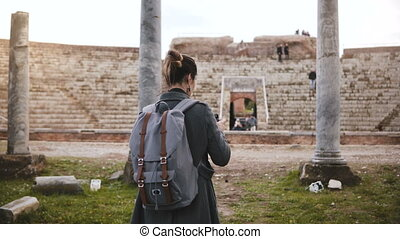 Back view of professional travel blogger girl with camera taking photo of ancient amphitheatre pillars in Ostia, Italy.