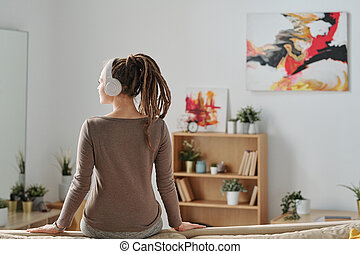 Back view of restful girl with dreadlocks sitting on sofa and listening to music