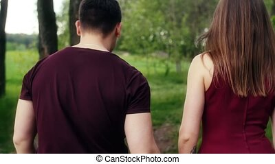 Back view of romantic young couple in love walking in forest, holding hands, talking and smiling. Steadicam shot slow mo