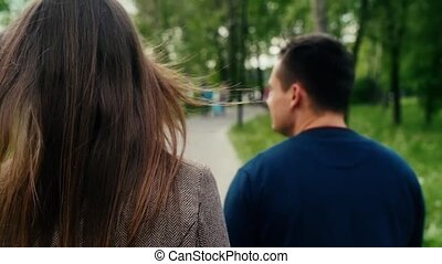 Back view of romantic young couple in love walking in park. Steadicam shot slow mo