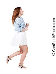 back view of running  woman. beautiful redhead girl in motion.