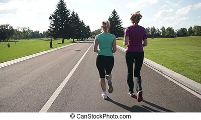 Back view of running women jogging in the park - Rear view...