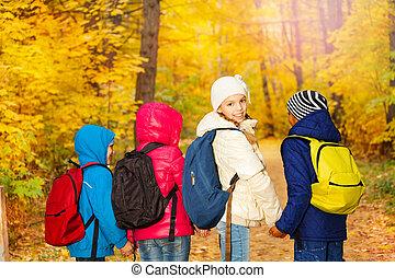Back view of schoolchildren holding hands in row