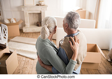 back view of senior couple hugging each other at new home
