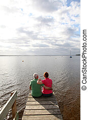 Back view of senior couple sitting on a pontoon