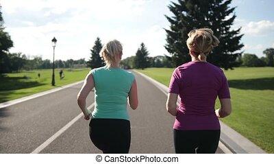 Back view of senior fitness women running on road