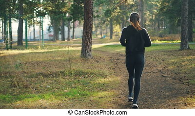 Back view of slender young woman in sportswear jogging in...
