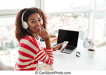 Back view of smiling african woman listening music by table