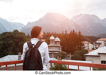 Back view of smiling hipster girl with backpack on mountains background