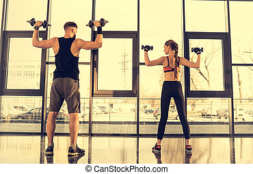 Back view of sporty man and woman exercising with dumbbells in gym