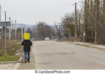 Back view of strong athletic man father carrying on shoulders young child in warm bright clothing walking along suburb road on cool spring foggy morning. Parents-children relations, love and care.