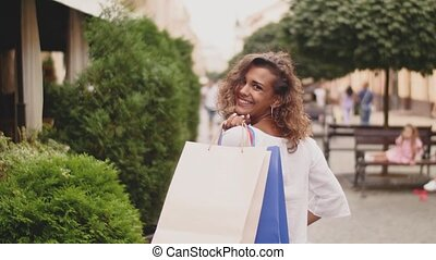 back view of stylish young woman with shopping bags walking on street