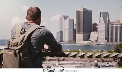 Back view of successful businessman standing and enjoying epic Manhattan skyline in sunny summer New York, slow motion.