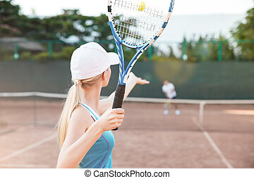 Back view of tennis player serving during a match. playing...
