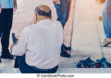 Back view of the old man with a bald head wearing shoes in front of the building.