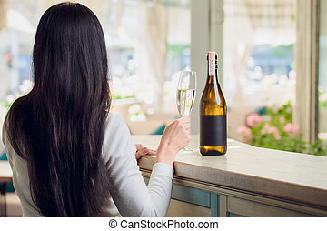 Back view of the woman sitting in cafe and looking in the...