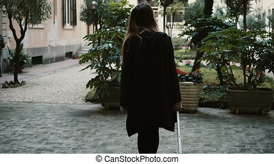 Back view of the young attractive woman with suitcase walking on the street. Female wearing black are coming in new city