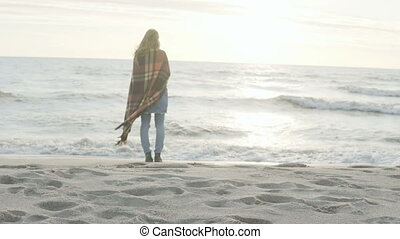 Back view of the young woman standing on shore of sea and looking into the distance. Lonely female enjoy the beach.