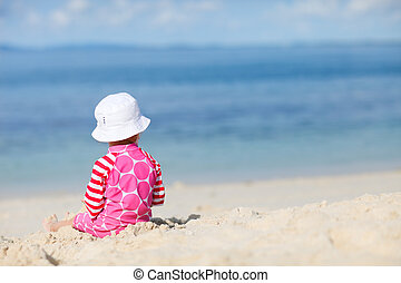 Back view of toddler girl playing with sand on tropical beach