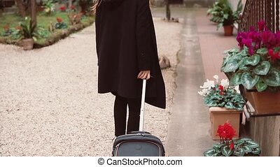 Back view of tourist woman in black. Close-up view of female legs walking with a suitcase in the street.