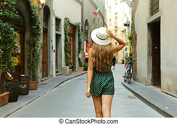 Back view of tourist woman walking in Florence street, Italy. Rear view of cheerful and happy girl in typical Italian old cozy street. Pretty beautiful tourist in Tuscany.