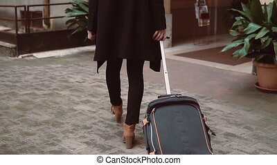 Back view of traveler woman legs walking with a suitcase in...