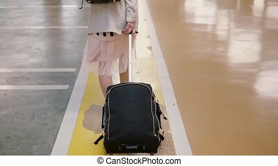 Back view of traveler woman legs walking with a suitcase in the airport. Girl with backpack flies on vacation.
