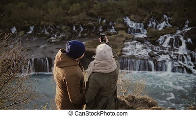 Back view of traveling couple standing near the waterfalls...