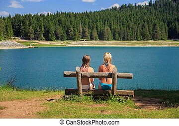 back view of two girls sitting on a bench near a mountain lake and pine trees