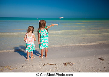 Back view of two little cute fashion sisters on the beach