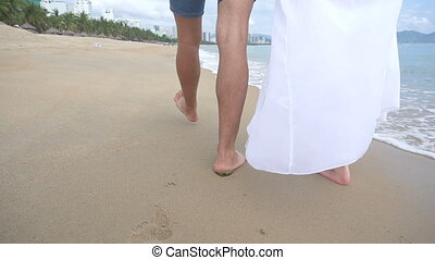 Back view of two lovers walking on the seaside and hugging. Legs on sand