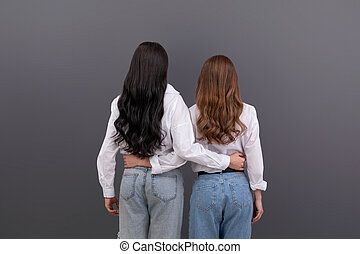 Back view of two unrecognizable women hugging each other. Friendship, family love concept.
