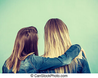 Back view of two women hugging