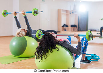 Back view of two women lifting barbell lying on stability ball while exercising in gym