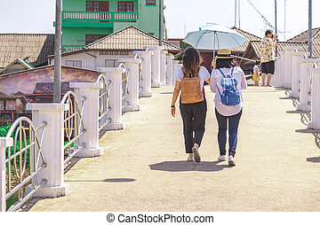 Back view of two women spread an umbrella to block the hot sun during the day to walk across the bridge together to visit the city.