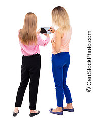 Back view of two young woman look at the smart phone. Rear...