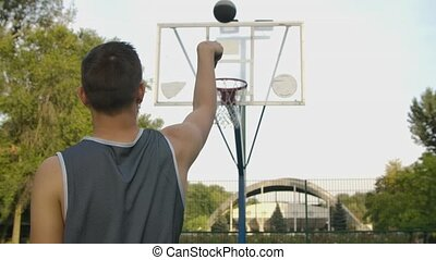 Back view of unrecognizable player throwing ball in a basketball hoop, the ball hits the ring and scores. Close up. Slow motion.