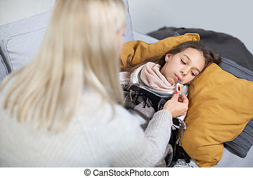 Back view of unrecognizable woman mother measuring temperature of her ill daughter. Sick child with high fever laying in bed and mother's hand holding thermometer in the girl's mouth