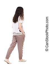 back view of walking curly woman. backside view of person....