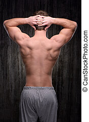 Back view of well formed man demonstrating back muscles
