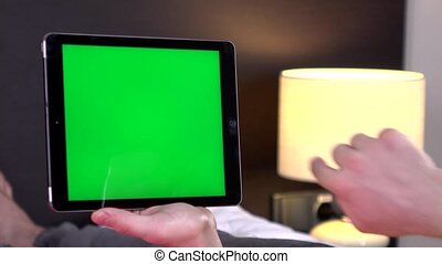 Back view of woman at home using electronic tablet, green screen