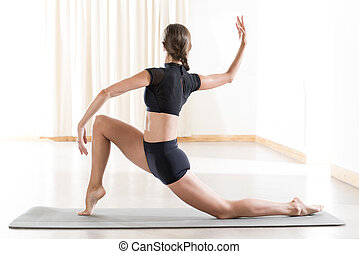 Back View of Woman in Black Crop Top Doing a Yoga Pose