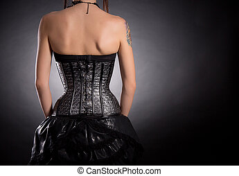 Back view of woman in silver leather corset
