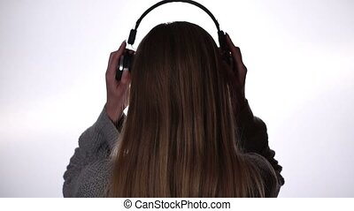 Back view of woman listening music in headphones