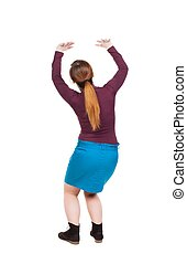 back view of woman protects hands from what is falling from abo