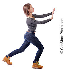 back view of woman pushes wall.