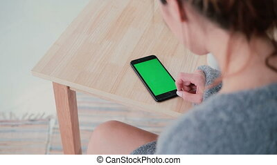 Back view of woman sitting at the table and drinking coffee in kitchen. Brunette girl uses smartphone, green screen.