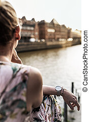 back view of woman sitting besides river in city
